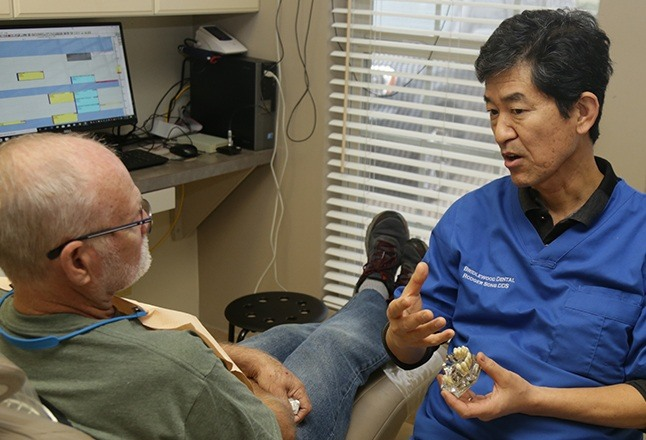Doctor song talking to dental patient