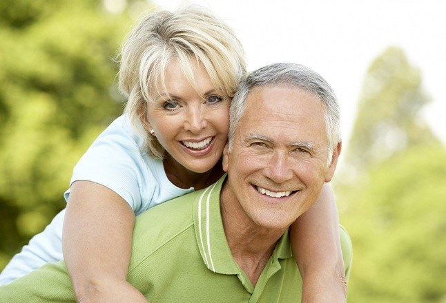 Older man and woman with dentures on golf course
