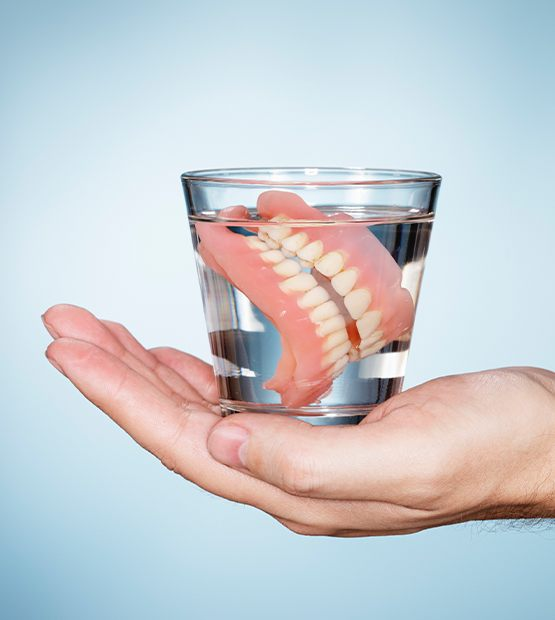 Hand holding glass of water with dentures