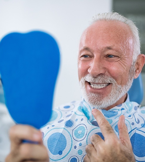 Man with dentures pointing to smile