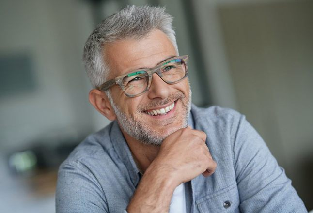 gray-haired man smiling with dental implants in Flower Mound