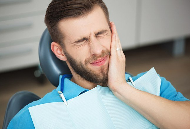 Man who needs to replace missing teeth holding cheek in dental office