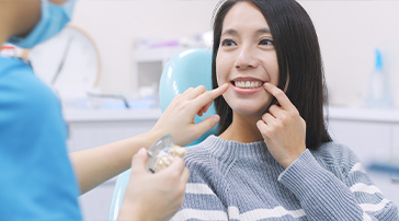 Woman pointing to her smile during preventive dentistry appointment