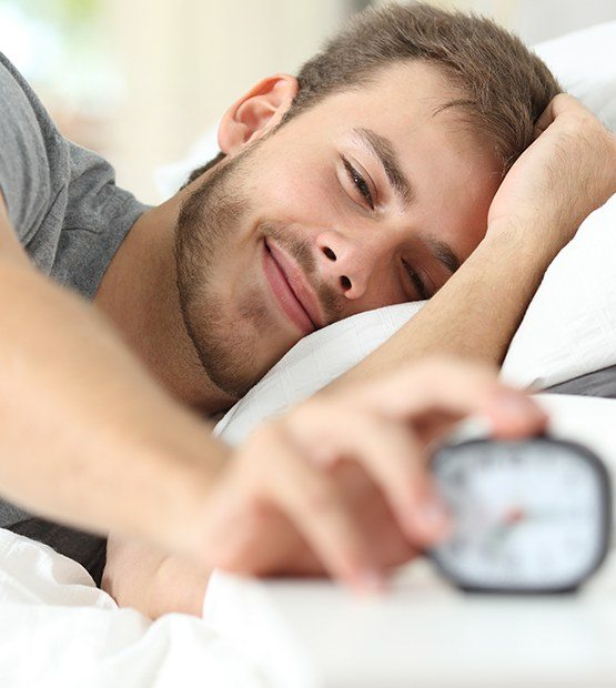 Man waking up feeling refreshed thanks to sleep apnea treatment