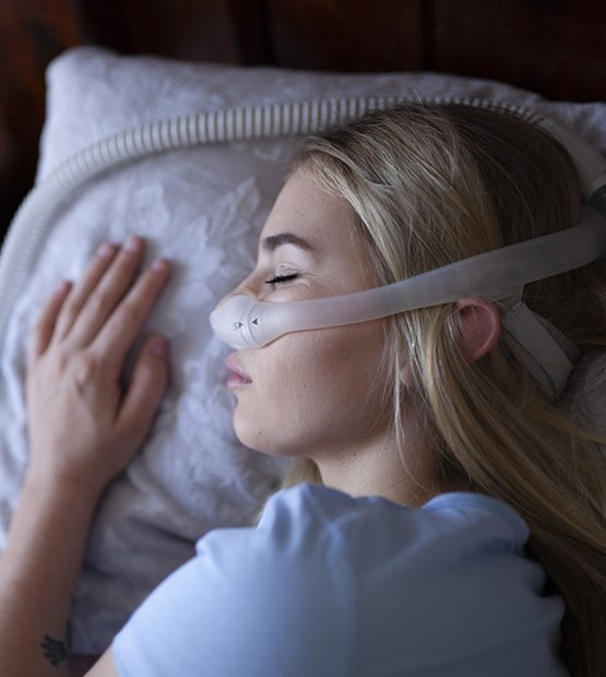 Woman using combined sleep apnea oral appliance and C pap treatment