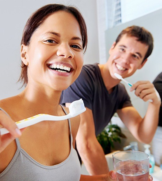 Man and woman brushing teeth after teeth whitening treatment