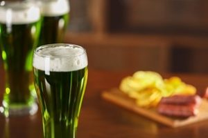 Green beers on a bar with food in the background