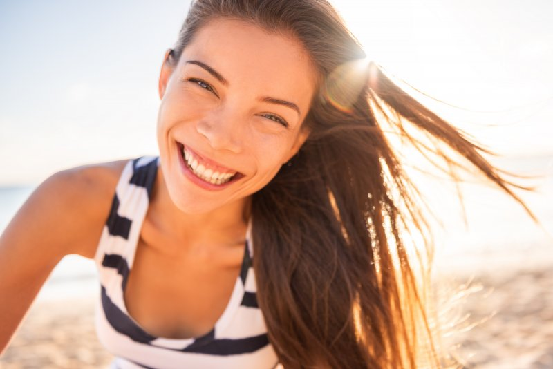 Woman in striped shirt smiling on the beach