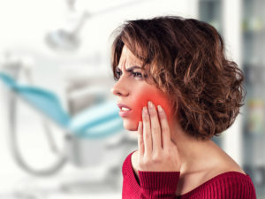 Woman with mouth pain from failed dental implant